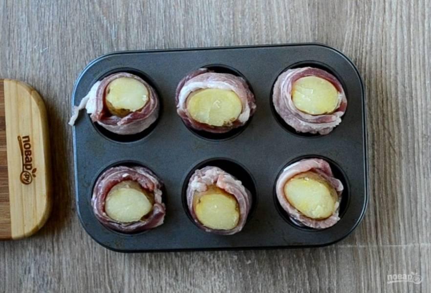 На каждой картофелине срежьте примерно 1 см от верхнего края. Каждую картофелину заверните в ломтик бекона и положите в форму для выпекания кексов.