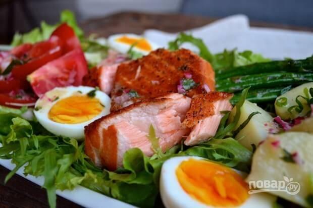 Добавьте картошку, порезанную половинками, яйца, помидоры, спаржу, лосось сверху (вилкой разделите его на несколько кусочков).  Полейте салат заправкой. Можете подавать.