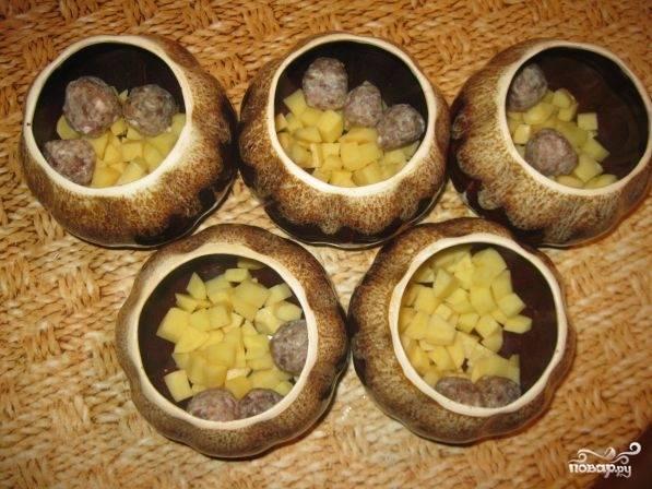 3. Горшочки можно смазать изнутри растительным маслом, но можно обойтись и без этого. На дно выложить картофель. Сверху положить фрикадельки.