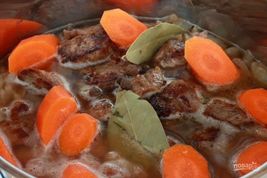 5.Влейте вино, выложите обратно мясо, нарезанную кусочками морковь, лавровый лист, душистый и черный перец, посолите. Влейте воду, чтобы она еле покрыла все содержимое. Доведите до кипения и тушите на слабом огне под закрытой крышкой 1 час.