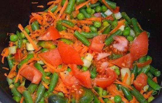 Закрываем крышку и готовим 10 минут. Можно 1-2 раза перемешать. Добавляем промытый рис и порезанный средними кусочками  помидор.