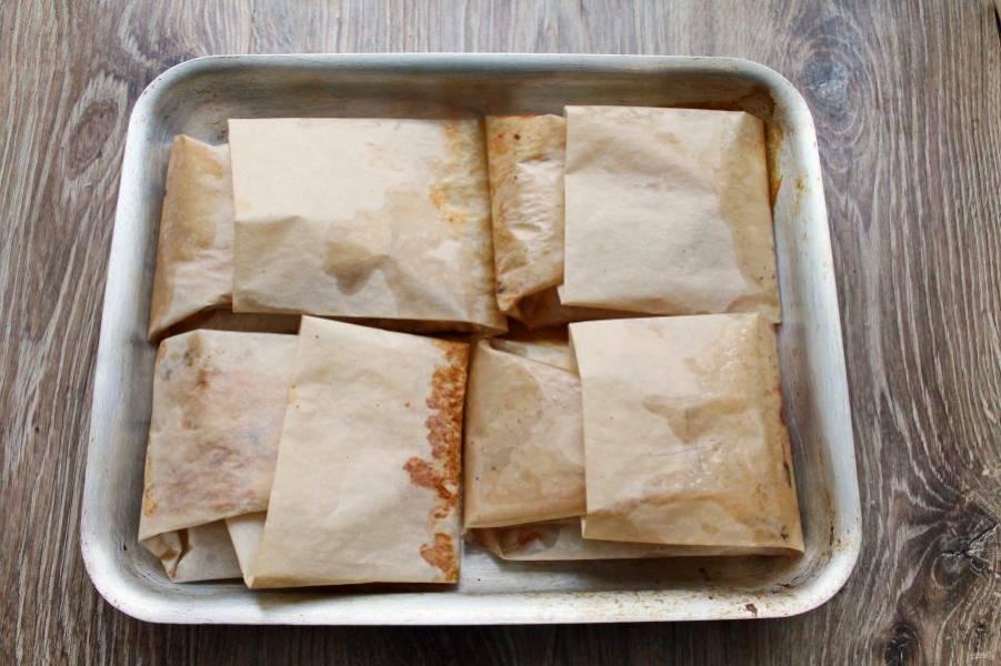 Поставьте в горячую духовку и запекайте при температуре 180 градусов в течение 25-30 минут, в зависимости от толщины кусочков рыбы. Достаньте противень из духовки и подавайте рыбу сразу прямо в пергаменте.