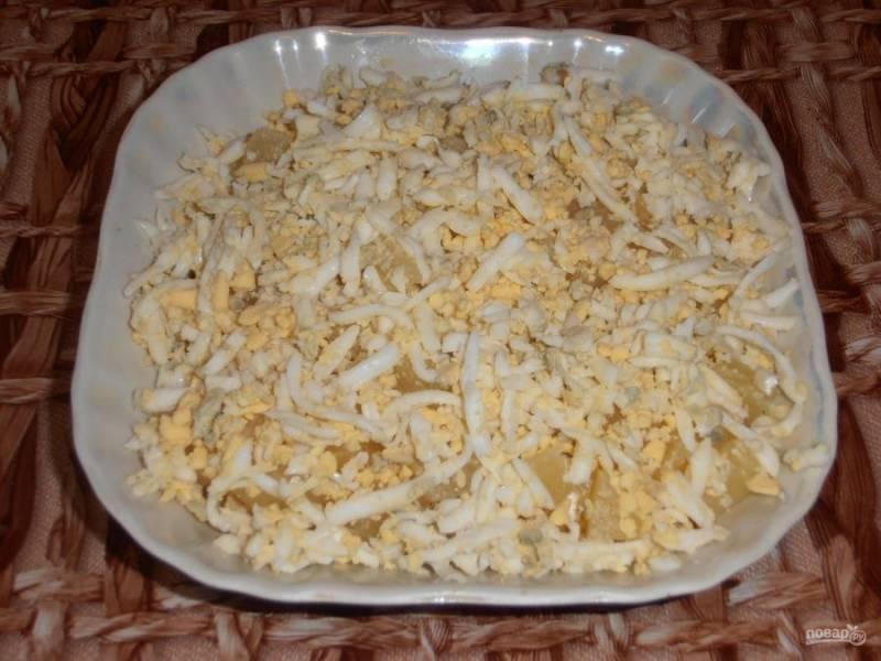 Сваренные вкрутую яйца очищаем и трем на терке. Присыпаем яйцами ананасы.