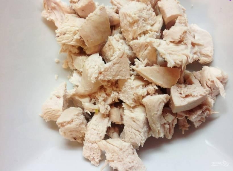 1. Отвариваем куриное филе, после чего охлаждаем его и нарезаем кусочками среднего размера (способ шинковки можно выбрать любой).