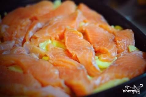 3. Форель очистить и порезать небольшими порционными кусочками. Ровным слоем выложить на картофель. Посолить и можно поперчить по вкусу.