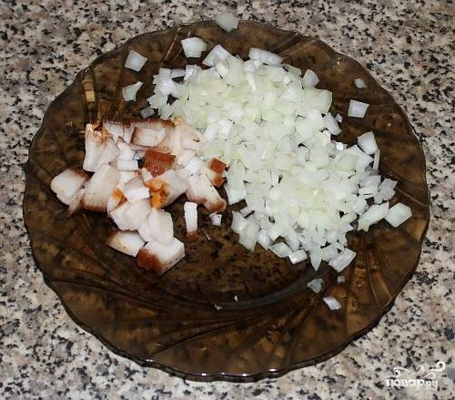 Почистите и нашинкуйте лук. Шпиг мелко нарежьте. Обжарьте их вместе на сковороде в масле до золотистого цвета. Добавьте немного соли.