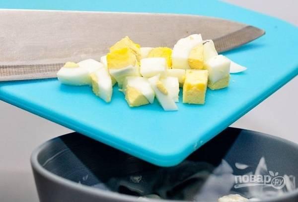 5. Очистите яйца, нарежьте их кубиками. Добавьте в салатник и аккуратно перемешайте. Нарежьте мелко сладкий перец, присыпьте им салат при подаче. Лучше всего отправить салатик в холодильник на полчасика-часик, прежде чем ставить его на стол.