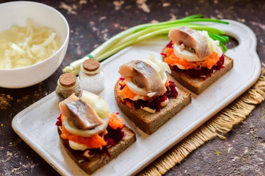 Завершающий акцент - выложите по кусочку селедки на яйцо, добавьте немного маринованного лука. Бутерброды можно подавать к столу.