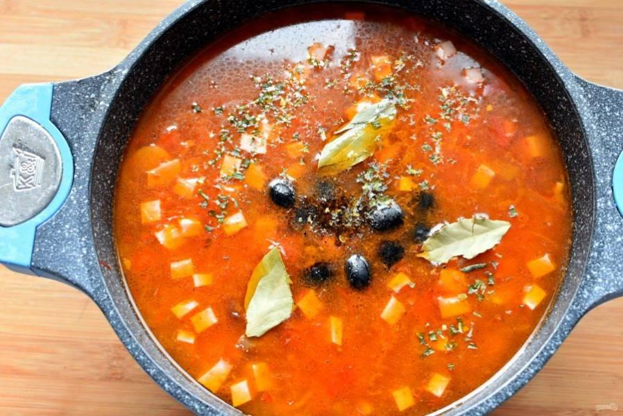 Переложите содержимое сковороды в кастрюлю с грибами. Добавьте маслины, отрегулируйте солянку на соль. Всыпьте  крупно растолченный черный перец, добавьте лавровый лист и  сушеную зелень. Доведите суп до кипения и снимите с огня, накройте крышкой и дайте настояться не менее 20 минут.