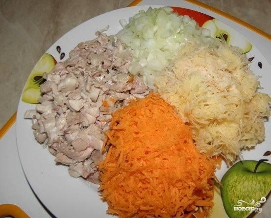 Окорочок положите в кастрюльку, залейте водой и отварите, предварительно немного подсолив воду. Затем остудите его и обберите с кости мясо, мелко его порубив. Натрите на терке очиненный лук, морковь и картофель. Все овощи для блюда должны быть свежими.