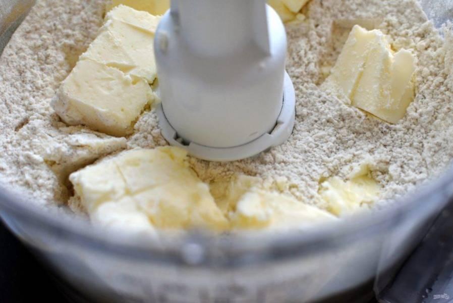 Я всегда делаю песочное тесто в комбайне – это очень удобно, быстро и хорошо. В чашу комбайна высыпьте просеянную муку, добавьте отруби, сахар, соль и разрыхлитель. В пульсовом режиме пробейте в крошку. Затем добавьте желток и снова включите комбайн. Постепенно добавьте  ложку-другую ледяной воды, пока тесто не соберется в шар. Заверните тесто в пленку и уберите в холодильник – не   морозилку – на  полчаса.