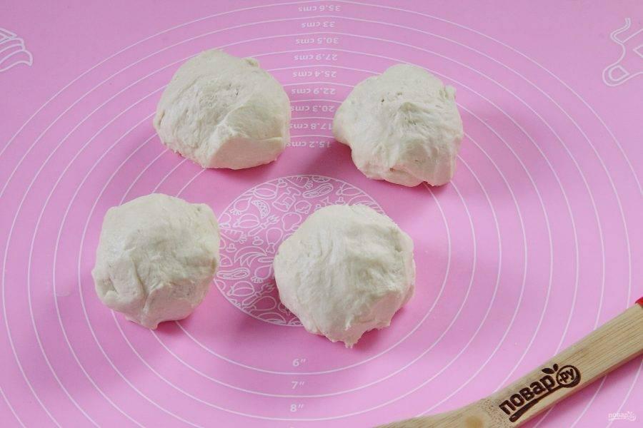 По истечении часа достаньте тесто из холодильника и разделите его на 4 части.
