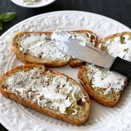 На каждый кусочек хлеба намазываем немного козьего сыра.