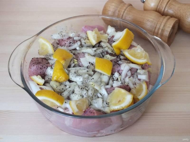 В глубокую чашку выложите мясо. Добавьте измельченный лук, свежемолотый перец, сок лимона и кусочки лимона. Всё хорошо перемешайте, как бы перетирая мясо.