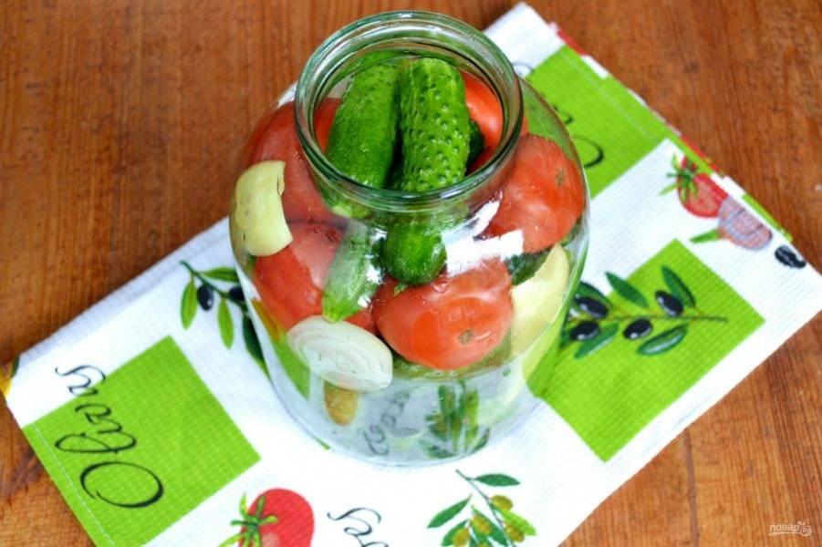 Заполните баночку огурчиками и помидорами. В образовавшиеся просветы поместите кусочки лука и сладкого перца.