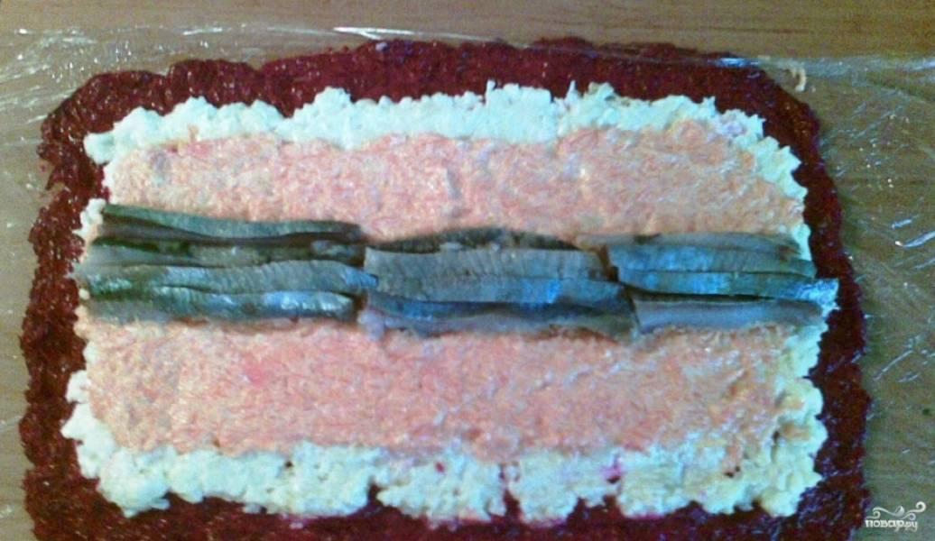 2. Дальше морковку тоже трем на терке, смешаем с майонезом и выкладываем поверху. И увенчиваем эту композицию кусочками селедки без косточек. Дальше аккуратно сворачиваем рулет.
