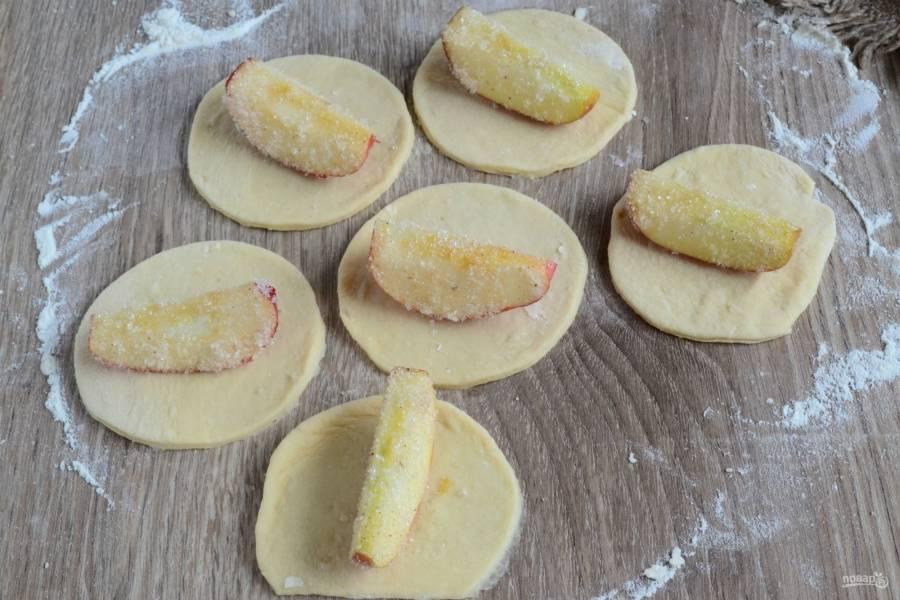 Яблочные дольки обваляйте в сахаре и положите на каждый кружок теста.