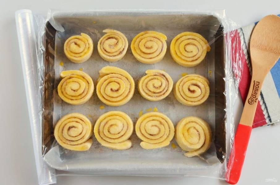 Накройте пищевой пленкой булочки и оставьте в тепле на 30 минут. За это время разогрейте духовку до 180 градусов.