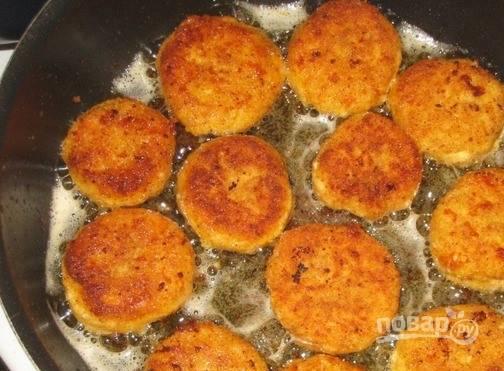 В сковороде разогрейте подсолнечное масло без запаха. Набирайте сырную массу ложкой и обваливайте в панировочных сухарях, формируя лепешки. Обжаривайте сырники на среднем огне с обеих сторон каждый до румяной корочки.