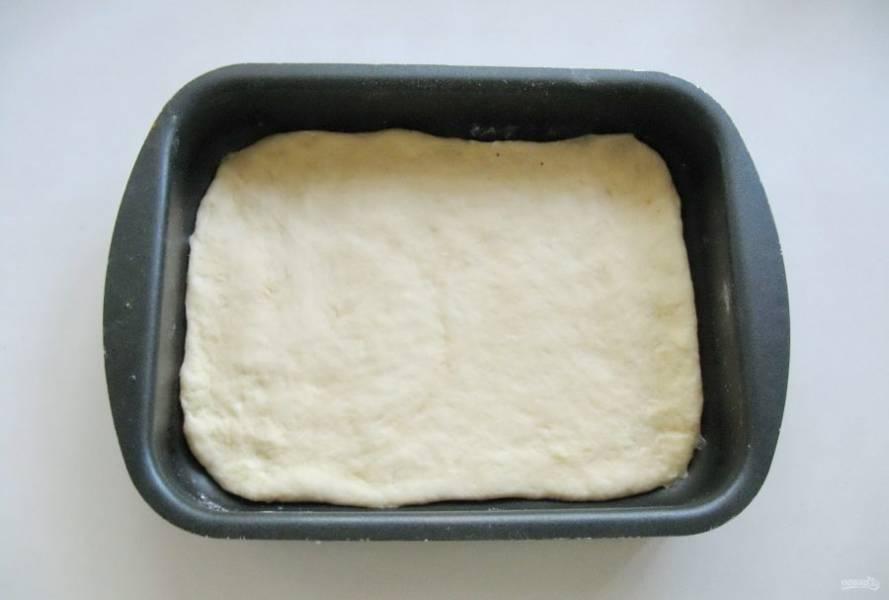 Разделите тесто на две неравные части. Большую часть раскатайте в пласт и выложите в форму для выпечки.