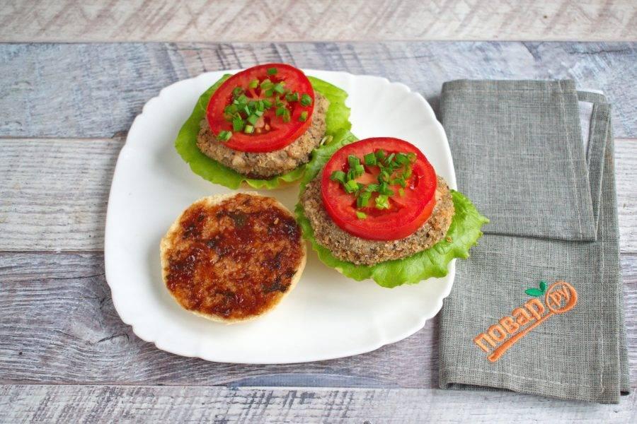 Теперь можно собирать веганский бургер. Половинку булочки смажьте ткемали (или другим соусом на ваш вкус), положите лист салата, овощную котлетку, измельченный зеленый лук, ломтик помидора.