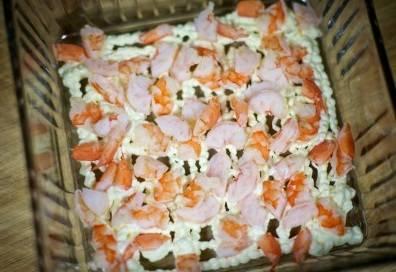 7. Креветки очистите, разрежьте, если они очень крупные и поделите общее количество на две части. Одну часть выкладываем в салатницу на сетку из майонеза.