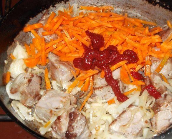 Готовое мясо извлекаем из бульона, нарезаем кусочками и обжариваем на растительном масле. Добавляем нарезанные лук и морковь, а также томатную пасту. Тушим до готовности овощей.