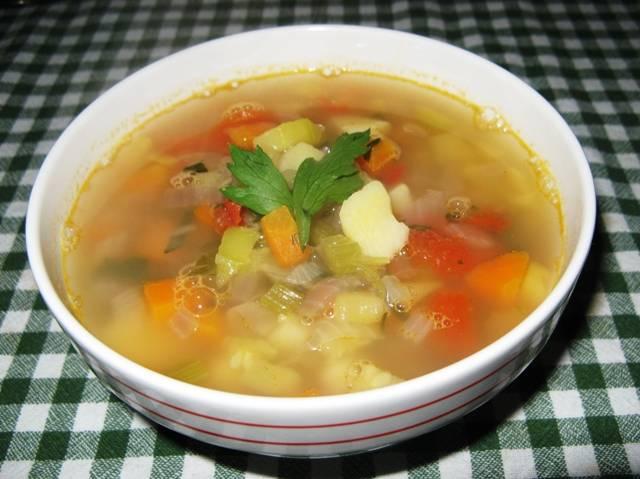 Когда кубики в воде растворяться, выкладываем в кастрюлю картофель, кабачок, морковь, лук, сельдерей, фасоль и чеснок. Оставляем суп вариться на 40-50 минут. За 10 минут до готовности солим и перчим его, добавляем помидор и измельченную зелень. Когда суп будет готов, вливаем в него 2 столовые ложки оливкового масла, перемешиваем и подаем к столу. Приятного аппетита!