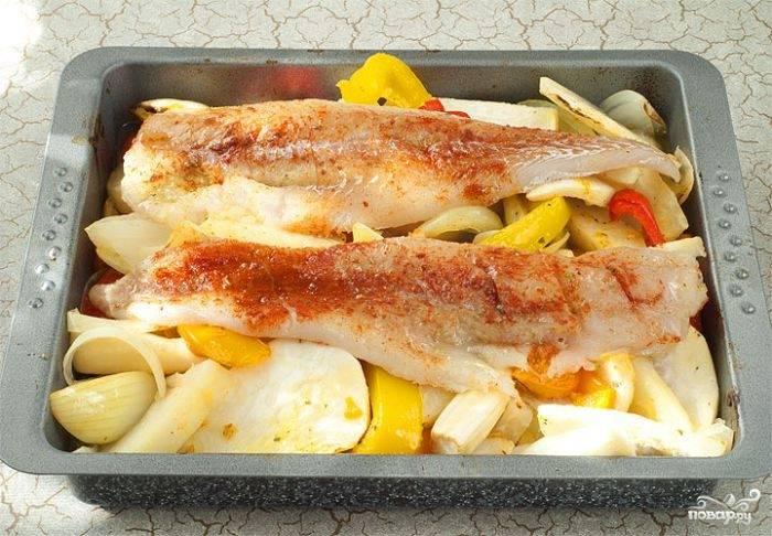 4. Аккуратно достаньте противень, выложите сверху овощей рыбку и отправьте обратно в духовку. Запекается минтай достаточно быстро, так как филе довольно тонкое.