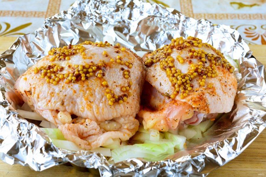 На форму для запекания выложите фольгу. Выложите слой лука, полейте растительным маслом. Сверху на луковую подушку распределите куриные бедрышки. Курицу дополнительно смажьте зерновой горчицей.