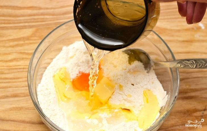 3. Вбейте один желток и влейте холодную воду.