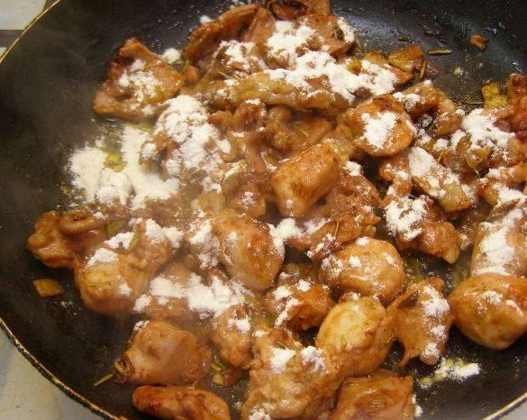 Посыпаем поджарившееся мясо мукой, перемешиваем и жарим минутку.