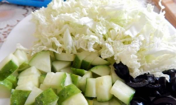 Промываем все овощи. Пекинскую капусту нарезаем тонкой соломкой. Маслины и огурец режем мелкими кубиками.