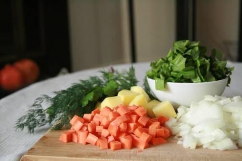 1. Подготовьте овощи. Морковь с картофелем очистите от кожуры и помойте. Картофель порубите ломтиками среднего размера, а морковь и лук — небольшими кубиками. В кастрюлю налейте растительное масло и обжарьте лук с морковью. Затем налейте воду и, после закипания положите в бульон картофель. Варите на среднем огне, снимая пену.