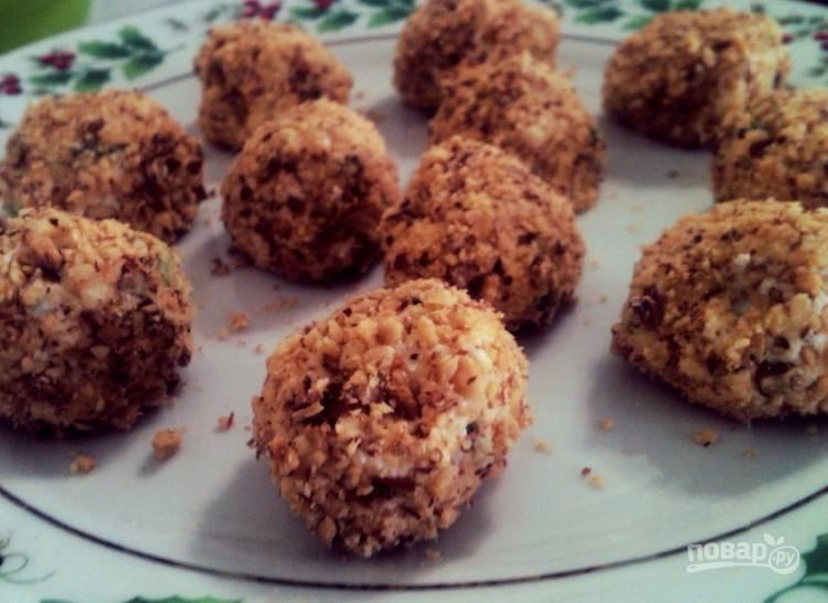 Затем сформируйте шарики из сырной массы, обмакните их в миндальную крошку со всех сторон.