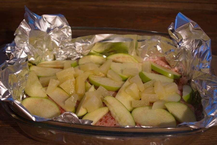 Яблоко и ананасы нарезать на кусочки и уложить поверх курицы. Полить все немного растительным маслом.