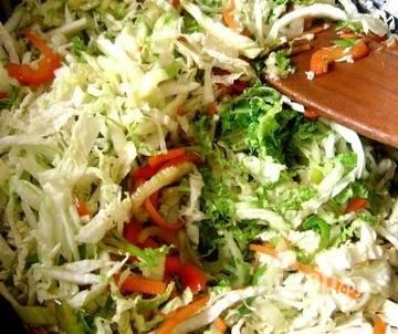 Пекинскую капусту нарежьте на продолговатые кусочки. Выложите ее к остальным овощам. Обжаривайте пару минут на сильном огне, постоянно помешивая. Затем влейте к ингредиентам соевый соус, накройте крышкой и тушите пять минут.
