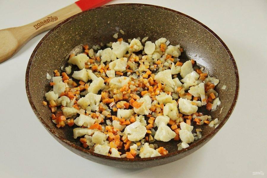 Соцветия цветной капусты разрежьте на несколько частей, добавьте в сковороду и обжарьте все вместе несколько минут.