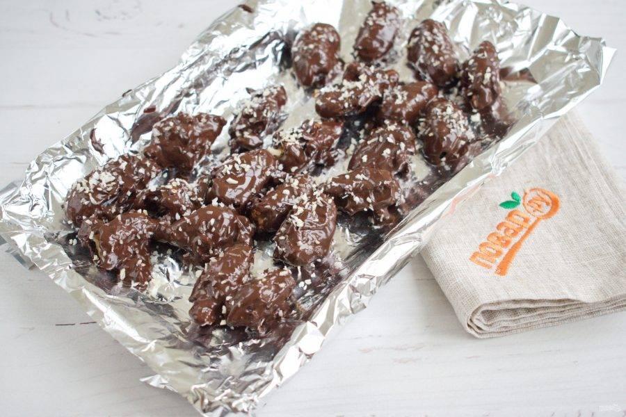 Окуните финики в растопленный шоколад, разместите на фольге. Шоколад на замороженных финиках быстро застывает. Посыпьте шоколад кокосовой стружкой. Поставьте в холодильник на 10-15 минут.