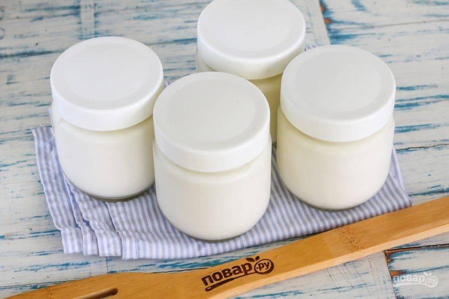 Затем перелейте заквашенную жидкость в небольшие баночки, закройте их крышками и укутайте полотенцем, оставляя при комнатной температуре на 2-6 часов. Еще лучше, если вы оставите баночки в тепле на ночь. Температура не должна быть выше 25 градусов и ниже 15 градусов, чтобы йогурт качественно заквасился. Затем перенесите емкости в холодильник на 1-2 часа для загустения.