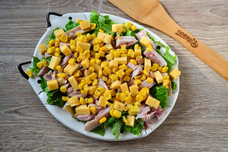 Далее выложите кубики сыра и кукурузу.