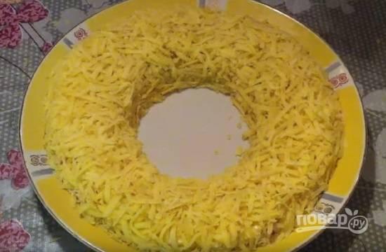 Теперь отжимаем уже маринованный лук и выкладываем его поверх мяса. Можно смазать майонезом, а можно сразу же на лук выложить слой натертой на крупной терке картошки.
