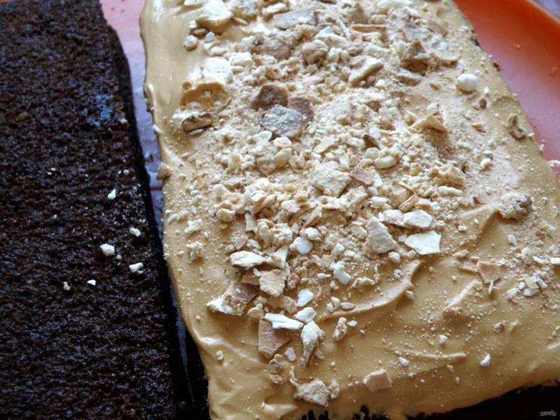 Намажьте половину крема на корж, присыпьте наломанными меренгами и накройте вторым коржом. Покройте кремом бока торта, уберите в морозилку до схватывания крема.
