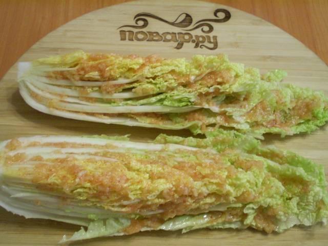Натрите капустные листья полученной кашицей. Сложите их в кастрюлю, поставьте гнет. Оставьте на 8-10 часов для засолки. Через 10 часов порежьте кусочками и подавайте на стол.