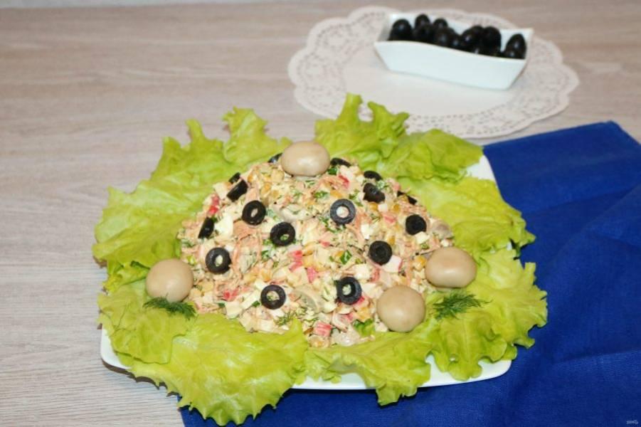 На большую тарелку выложите листья салата, сверху горкой распределите салат. Украсьте маслинами.