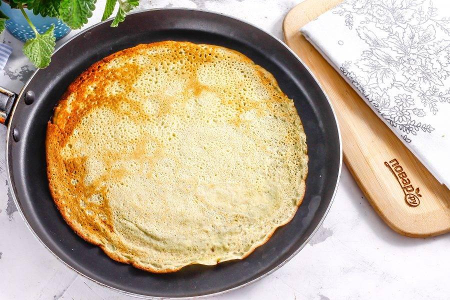 Прогрейте блинную сковороду и налейте на нее небольшую часть теста, сразу же округляя. Обжарьте блин с каждой стороны по 1 минуте и выложите на тарелку.