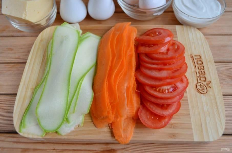 С помощью овощечистки порежьте кабачок и морковь тонкими слайсами. Помидор просто порежьте на колечки.