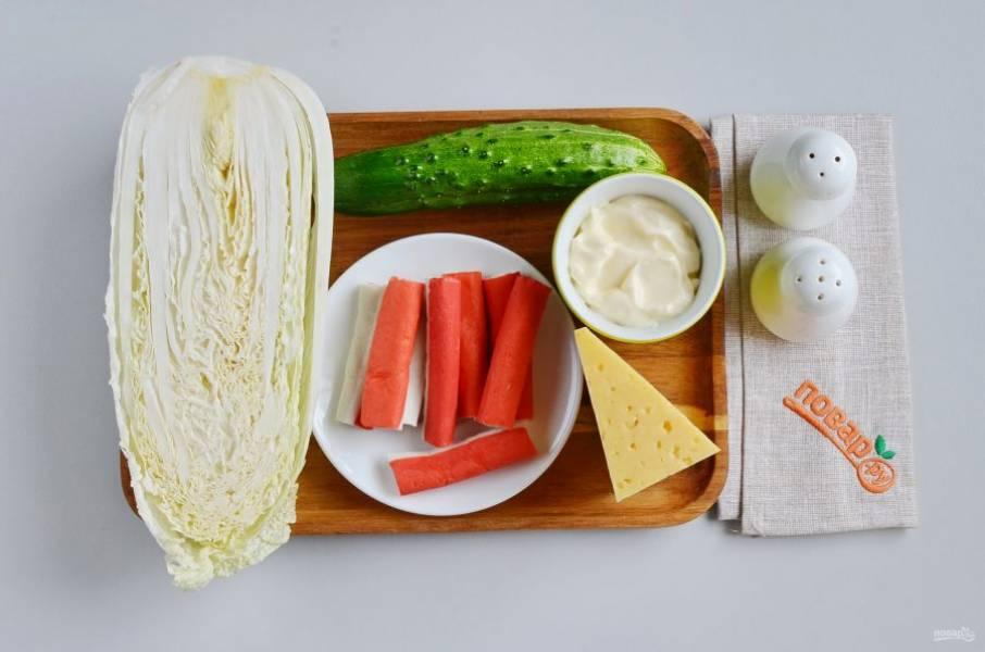 Подготовьте ингредиенты. Вымойте капусту и огурчик. Снимите целлофан с крабовых палочек.