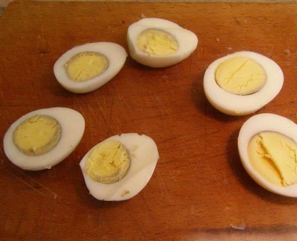 Сварите в крутую перепелиные яйца, очистите и разрежьте их пополам.