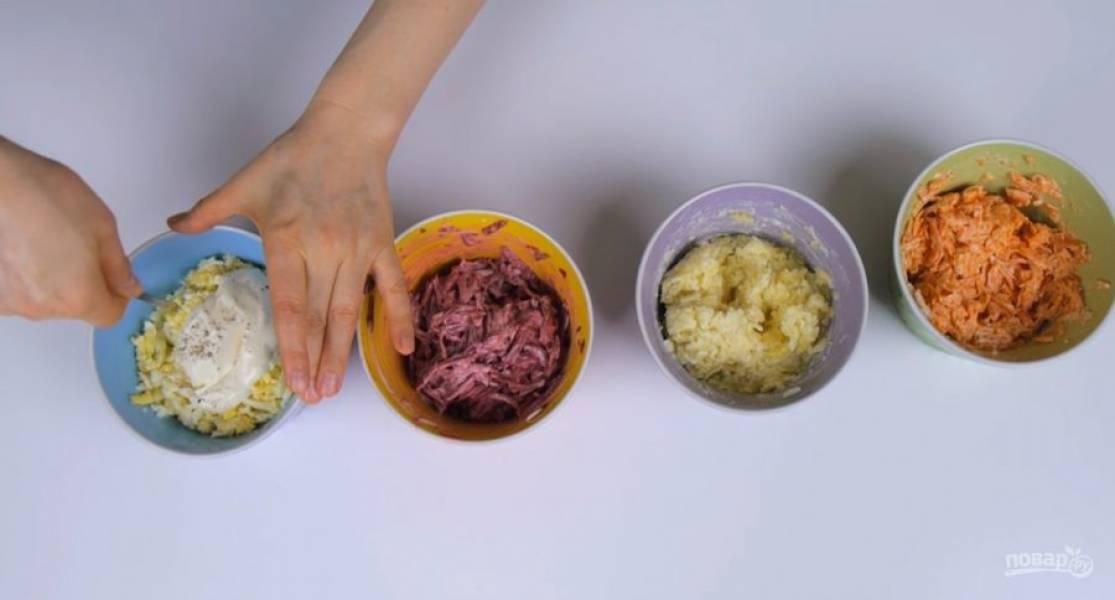 3.  Филе соленой сельди нарежьте кубиками. К натертым на крупной терке моркови, картофелю, свекле и яйцам добавьте майонез, подсолите и поперчите по вкусу. На блюдо установите кольцо от разъемной формы диаметром 21 см верхним краем вниз.